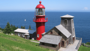Fame Point lighthouse in front of sea in Gaspesie